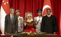 Singapore swears in first female president amid criticism