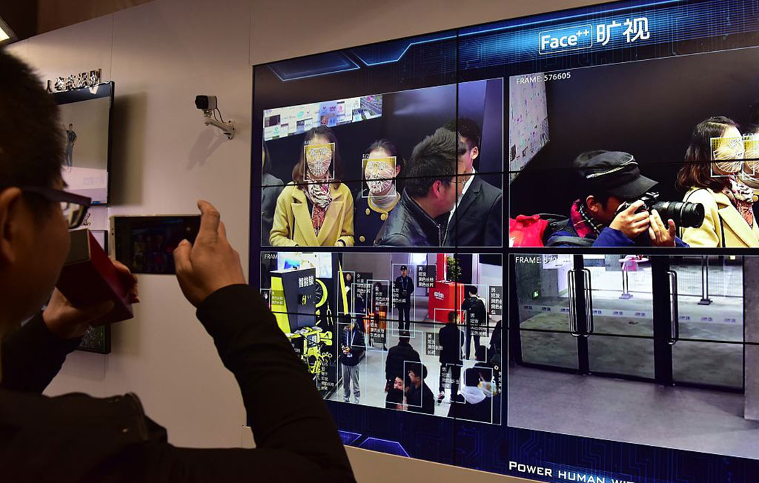 A visitor snaps a photo of video demonstrating a city surveillance system that features facial recognition technology.