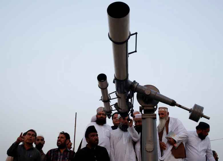 Members of the moon sighting committee gather and use telescope for the new moon that will mark the start of Ramadan, from Pakistan's Meteorological Department (PMD) building in Karachi, Pakistan. REUTERS