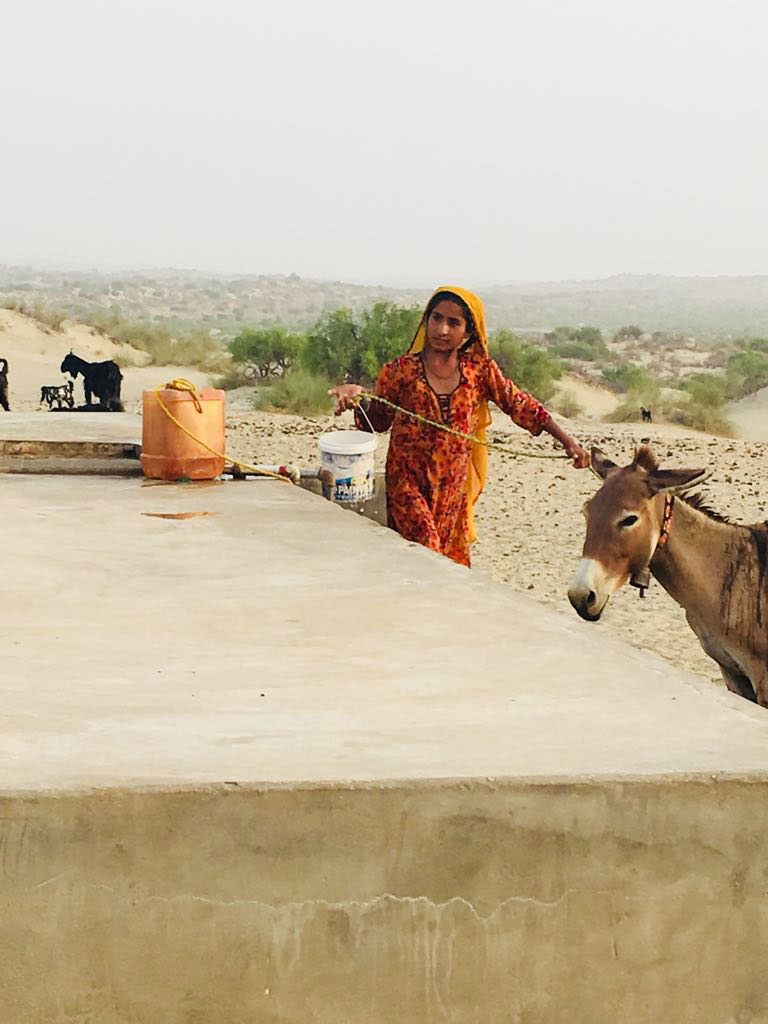 Young village-dweller pictured taking, storing water from a tank