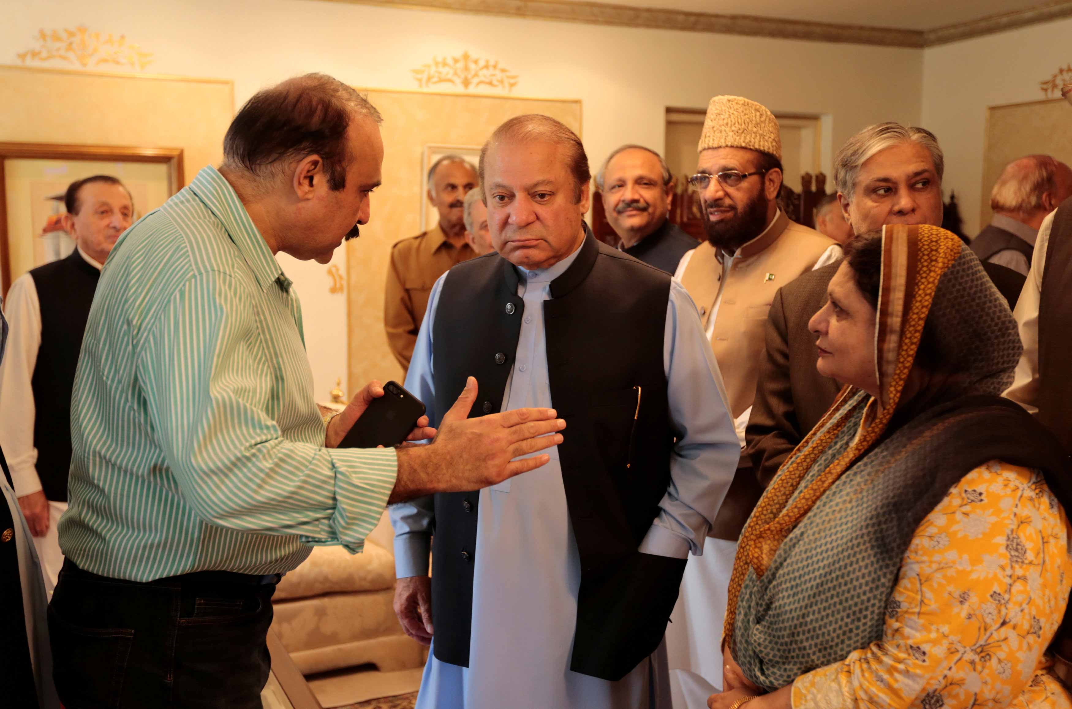 Former prime minister Nawaz Sharif speaks with members of his former cabinet as he prepares to leave Punjab House.