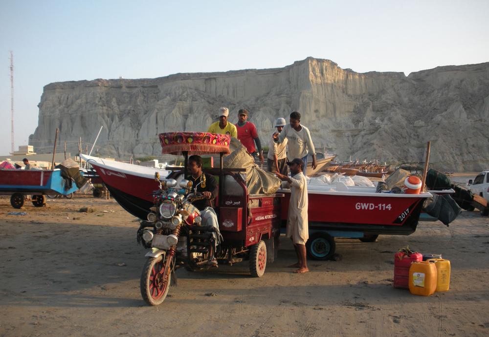 Pakistani fishermen move a boat in Gwadar port.
