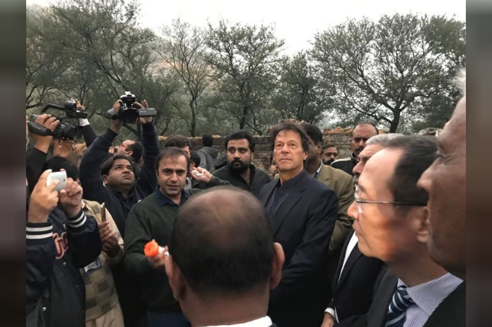 Imran Khan, chairman of the Pakistan Tehreek-e-Insaf (PTI) political party, along with the members of the media, looks on during the unveiling ceremony of the Buddhist-period archeological site near Haripur, in Khyber Pakhtunkhwa.