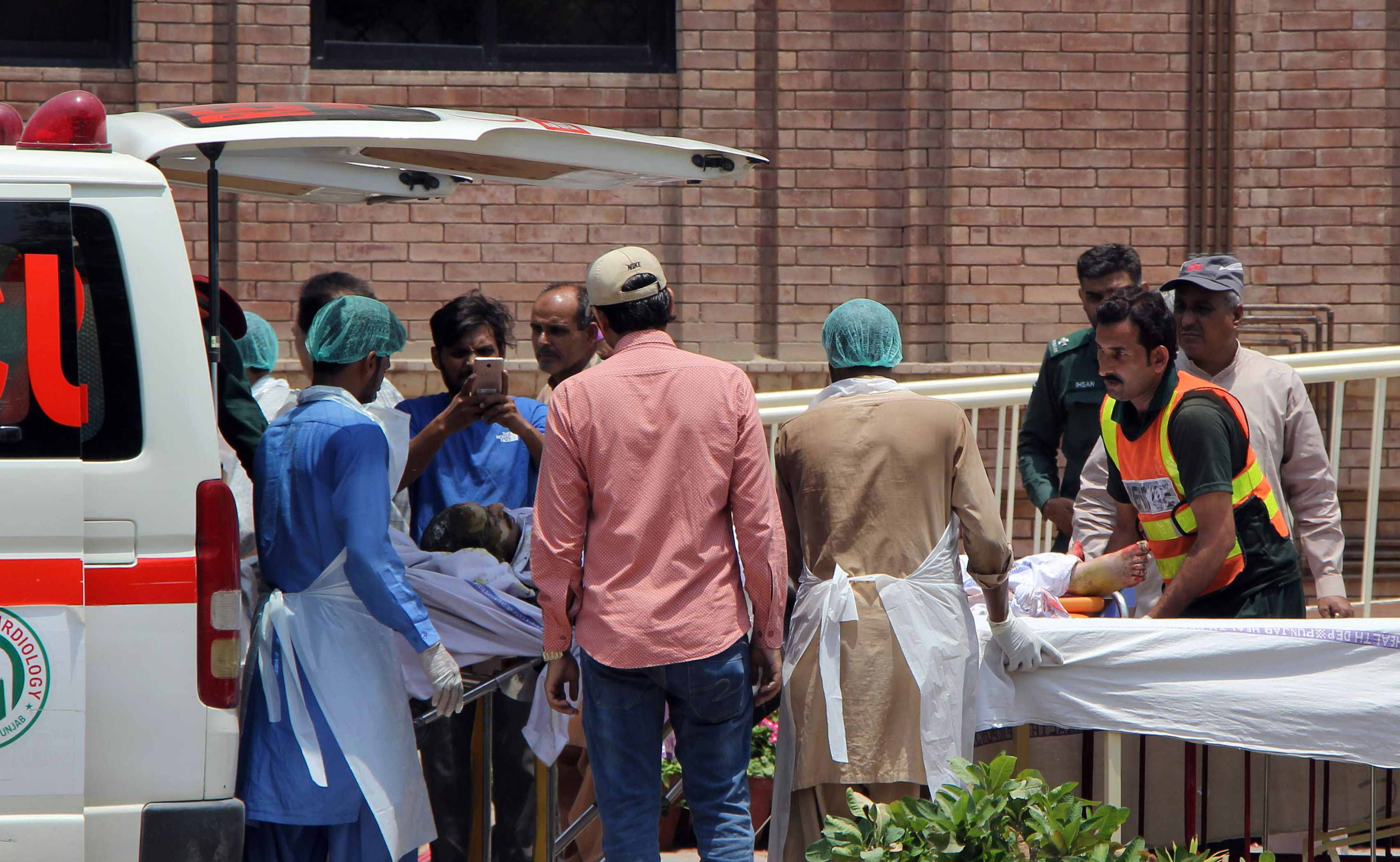 Paramedics bring a burns victim injured after an oil tanker caught fire following an accident on a highway in Bahawalpur to a hospital in Multan.