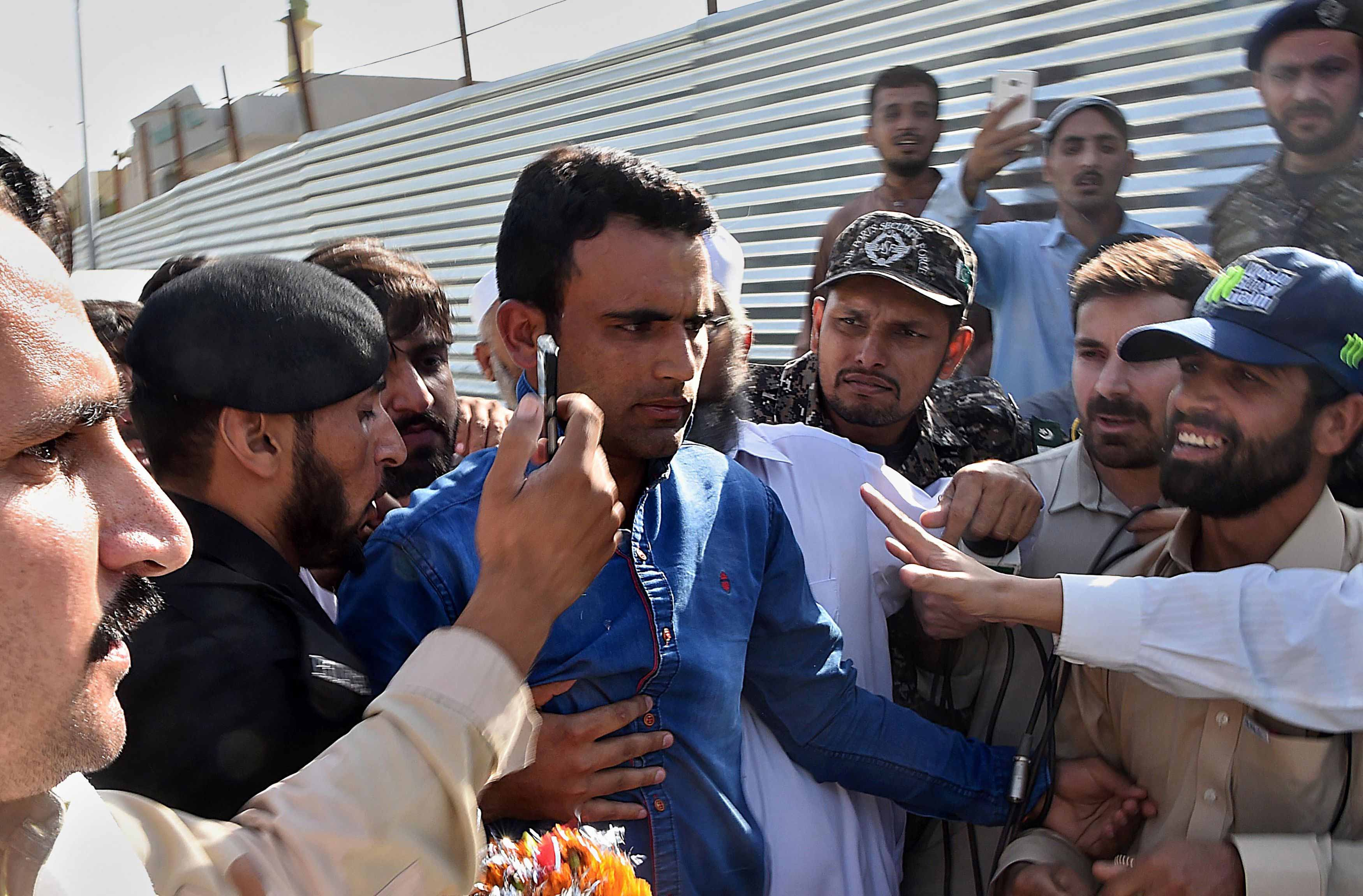 Fakhar Zaman (C) is surrounded by fans as he arrives from London outside the Bacha Khan International airport in Peshawar.
