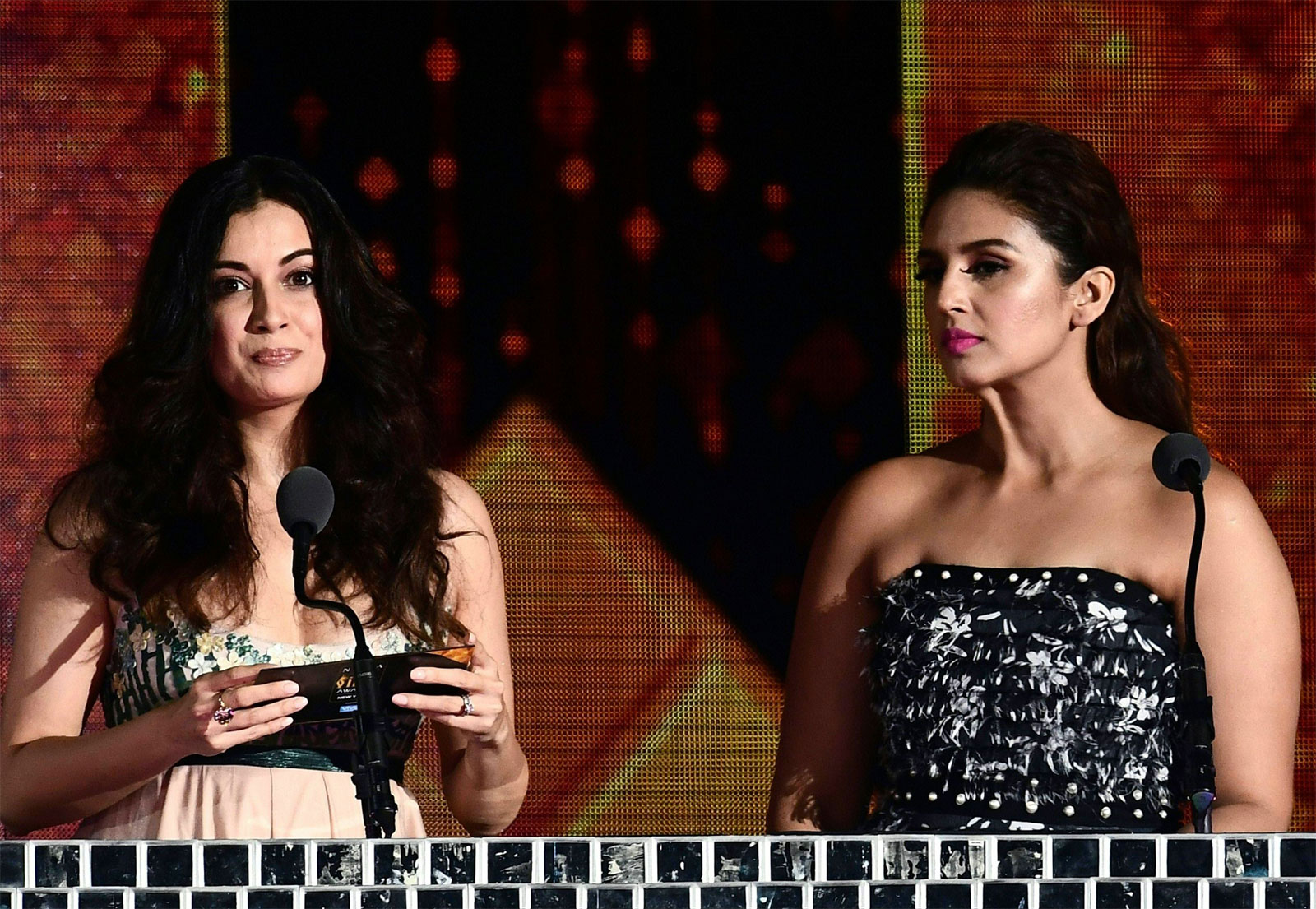 Dia Mirza (L) announces a winner as Huma Qureshi looks on during IIFA Rocks/AFP