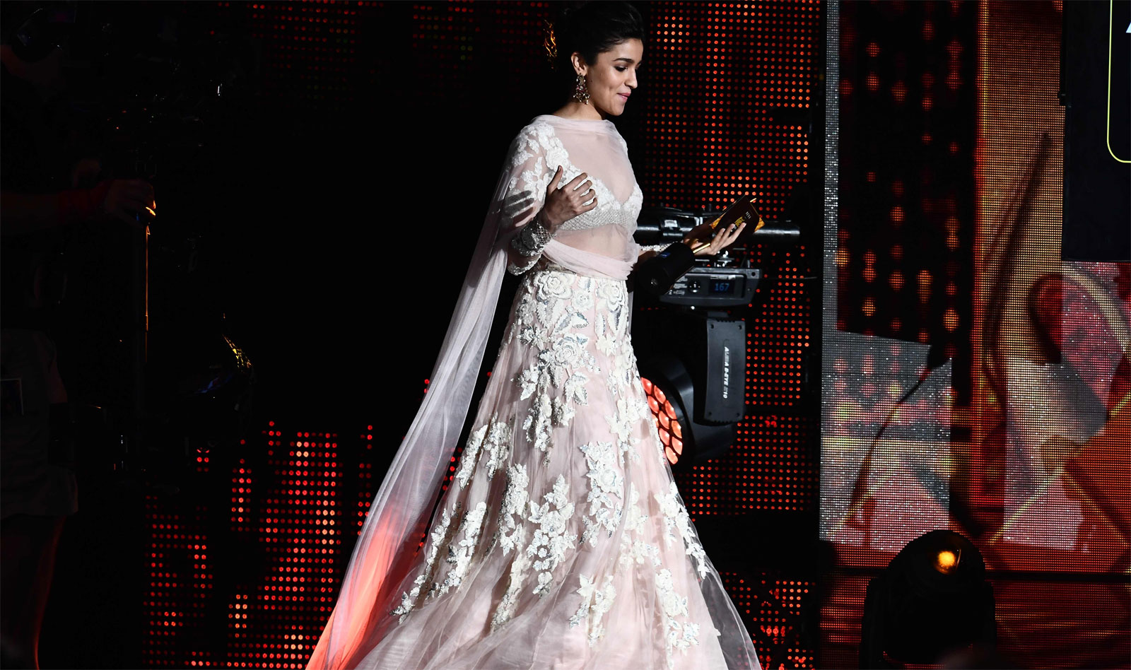 Alia Bhatt arrives on stage to give an award during IIFA Rocks 2017/AFP