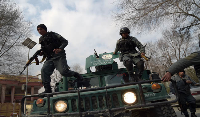 Afghan policemen leap from a vehicle as they arrive at the site of an explosion in Kabul