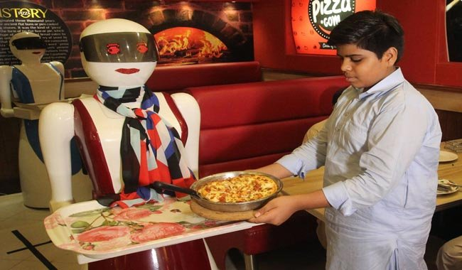A young customer picks up a pizza from a tray carried by a robot waitress