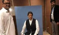 Imran borrows waistcoat from NA employee for card picture