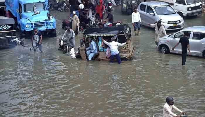 Vehicles passing through flooded street at Bufferzon after heavy monsoon rains in Karachi. -APP