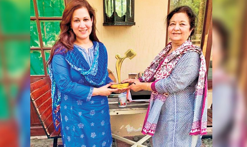 Ms Baela handing the CLF award to Shahdab Zeest Hashmi