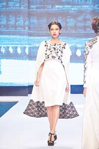 Aamna Aqeel The designer's monochrome collection for FPW titled Black on Fire consisted of some standout pieces, such as this tailored white cape with black detailing. The interesting cut, tasteful embroidery and the hint of black lace at the hem make it the perfect eveningwear choice for those of you looking to channel sexy sophistication when you hit the town this party season.