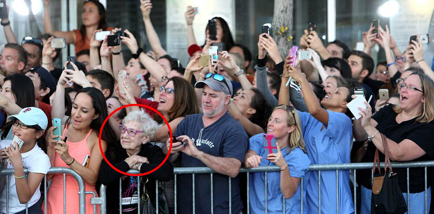 The photo that went viral: an old woman savours the moment while the crowd snaps pictures at a film premiere.