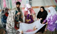 Iranian women roll infants in roses to keep them fresh and healthy