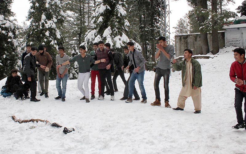Tourists enjoy themselves while playing with snow at Murree road, Nathiagali.