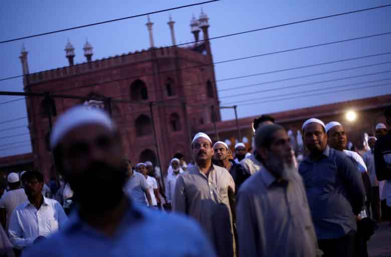 Muslim men look towards the sky to spot the crescent moon, on the eve of the holy fasting month of Ramadan, at the Jama Masjid (Grand Mosque) in the old quarters of Delhi, India. REUTERS