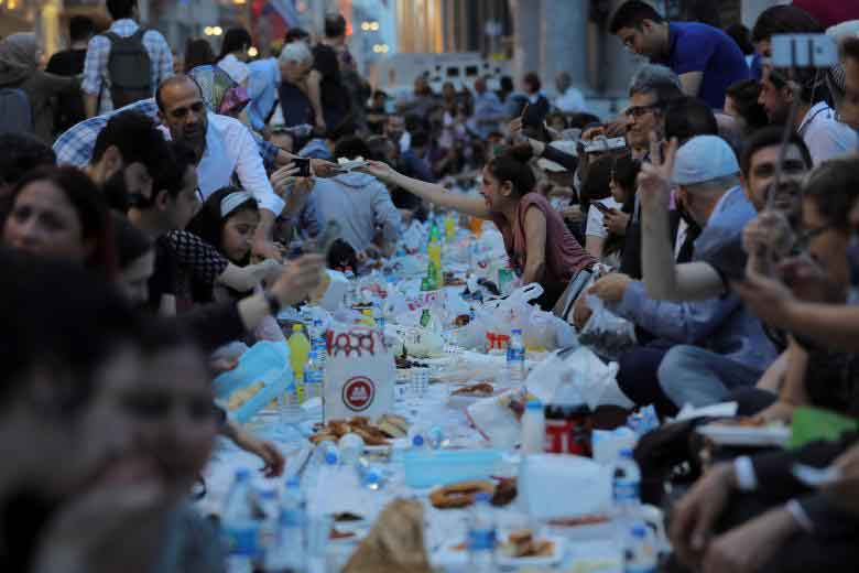People break their fast at the main shopping and pedestrian street of Istiklal on the first day of the holy fasting month of Ramadan in central Istanbul, Turkey. REUTERS