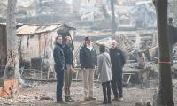 Trump visits fire-wracked California as more than 1,000 missing