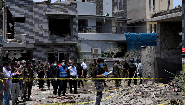 Security officials inspect the site of an explosion that killed at least three people and wounded several others in Lahore on June 23, 2021. — AFP