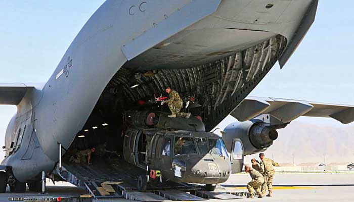 In this handout photo taken on June 16, 2021 and released on June 29, 2021 by the US Defense Visual Information Distribution Service (DVIDS) Aerial porters work with maintainers to load a UH-60L Blackhawk helicopter into a C-17 Globemaster III in support of the Resolute Support retrograde mission in Bagram.-AFP