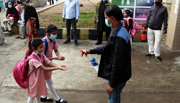 Students wearing face masks arrive at their school in Karachi, on February 2, 2021. — INP/File