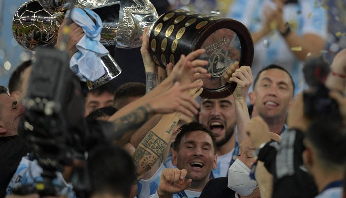 Argentinas Lionel Messi (C, bottom) holds the trophy as he celebrates with teammates after winning the Conmebol 2021 Copa America football tournament final match against Brazil at Maracana Stadium in Rio de Janeiro, Brazil, on July 10, 2021. Argentina won 1-0. — AFP