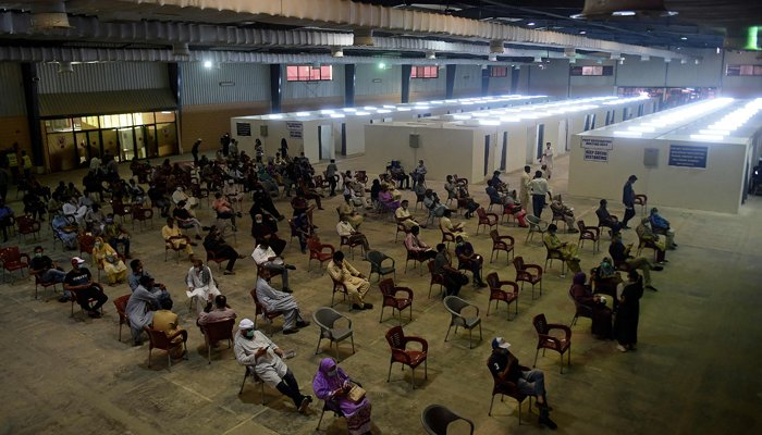 People wait for their turn to receive a dose of the coronavirus Sinovac vaccine at a vaccination camp organised at expo centre in Karachi on June 3, 2021. — AFP/File