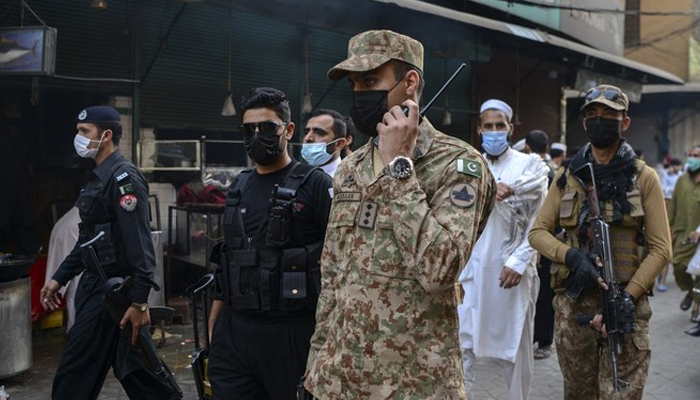Army soldiers patrol a market to implement new restrictions imposed as a preventive measure against the spread of the Covid-19 coronavirus in Peshawar on April 26, 2021. — AFP/File