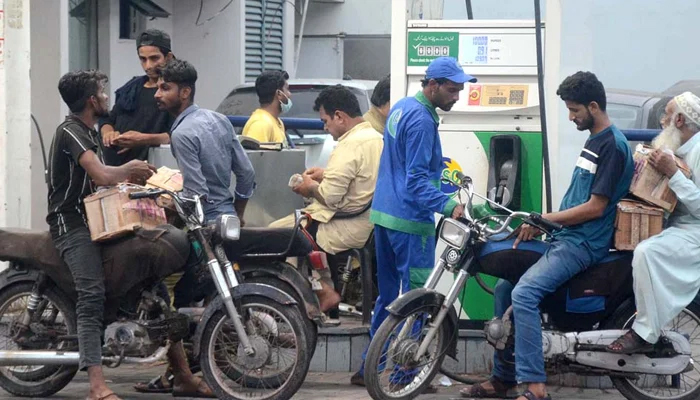 People getting their fuel tanks filled with petrol at a gas pump in Karachi, on May 28, 2021. — APP/File