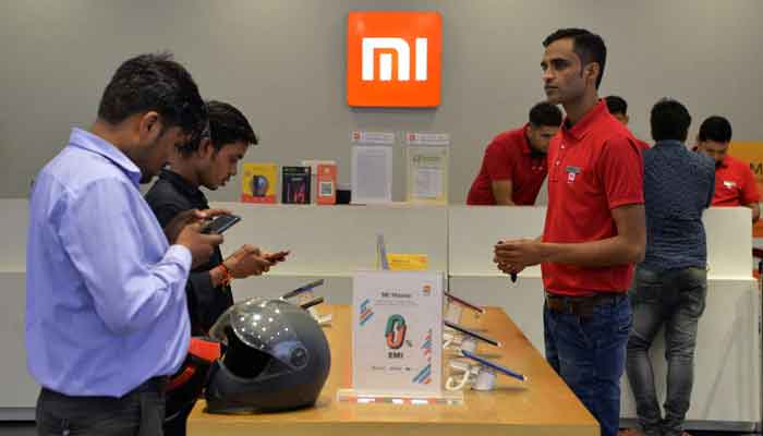In this file photo taken on August 20, 2019, customers inspect smartphones made by Xiaomi at a Mi store in Gurgaon, India.— AFP