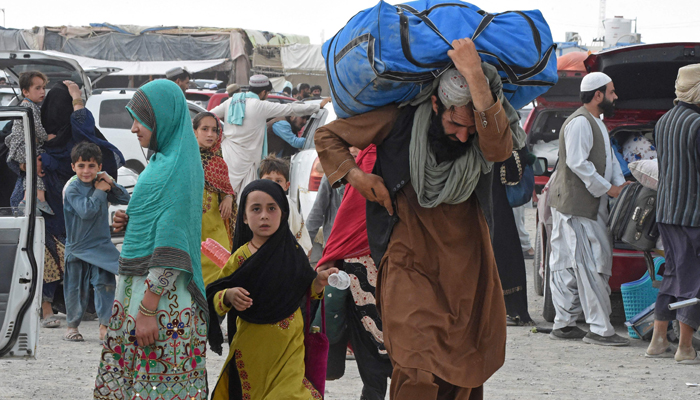 Pakistani people return from Afghanistan after crossing the border point in Pakistans town of Chaman on July 17, 2021. — AFP