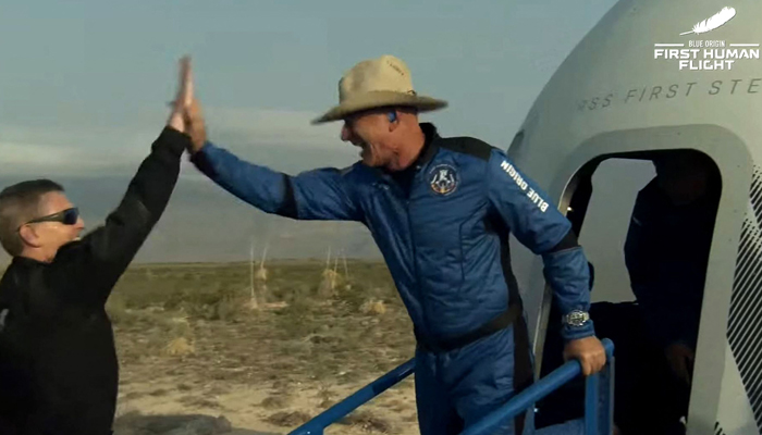 This still image taken from video by Blue Origin shows Jeff Bezos (R) celebrating after exiting Blue Origin´s reusable New Shepard craft capsule returned from space, safely landing on July 20, 2021. — AFP