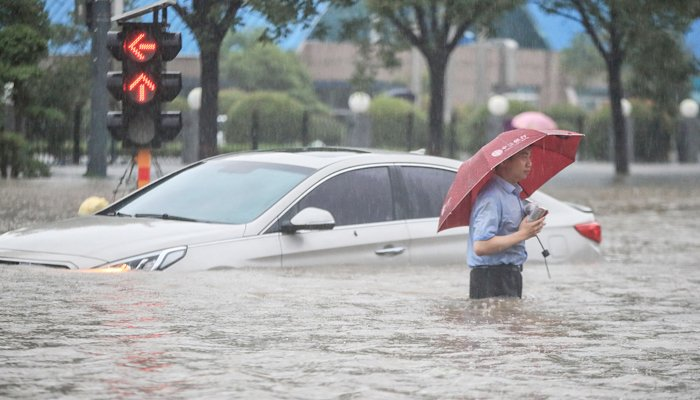 This photo taken on July 20, 2021 shows a man wading past a submerged car along a flooded street following heavy rains in Zhengzhou in China´s central Henan province. — AFP/File