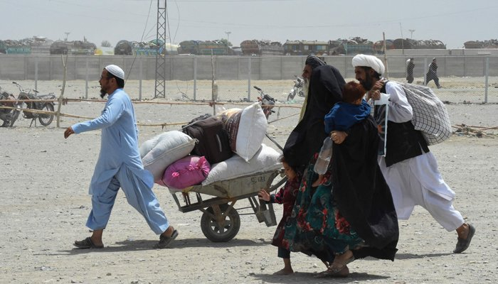 People walk towards a border crossing point in Pakistans border town of Chaman on July 17, 2021. — AFP