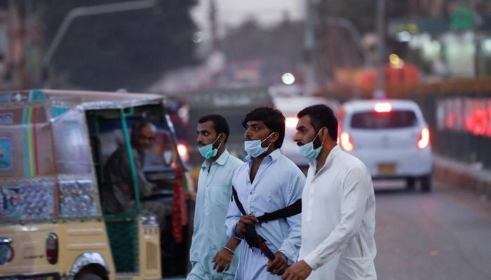 Men walk on the road without wearing masks properly. Photo: File