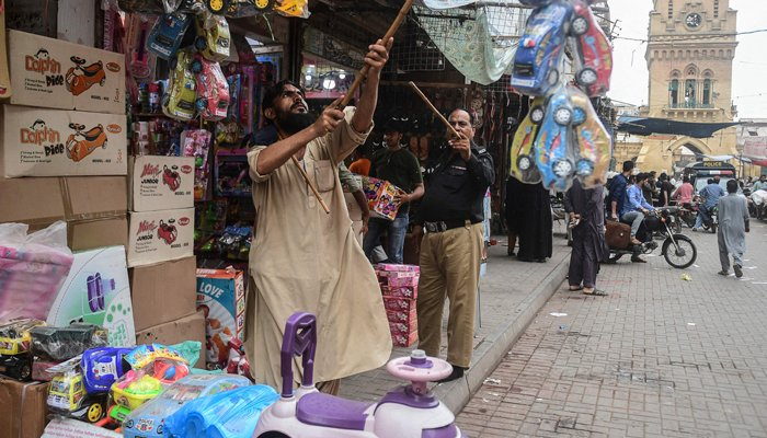 A policeman orders shopkeepers to close their shops after authorities imposed evening lockdowns amidst rising Covid-19 coronavirus cases in Karachi on July 26, 2021. — AFP/File