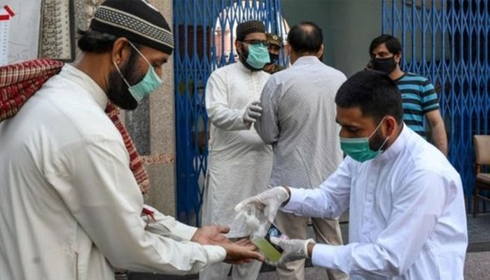 An official providing a man with sanitizer before entering a building. Photo: File