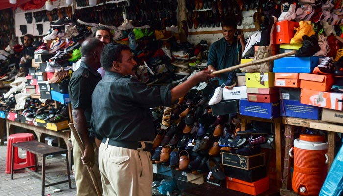 Policemen order shopkeepers to close their shops after authorities imposed evening lockdowns amidst rising Covid-19 coronavirus cases in Karachi on July 26, 2021. — AFP/File