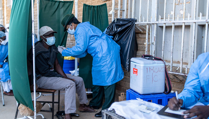 A military personnel inoculate a dose of SinoVac vaccine to a citizen at a mobile clinic in Emganwini township, Bulawayo, Zimbabwe on 3 August 2021. — AFP/File