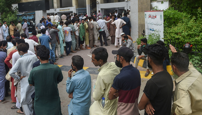 People queue up and wait to get themselves inoculated with the COVID-19 coronavirus vaccine at a vaccination centre in Karachi on August 1, 2021. — AFP/File