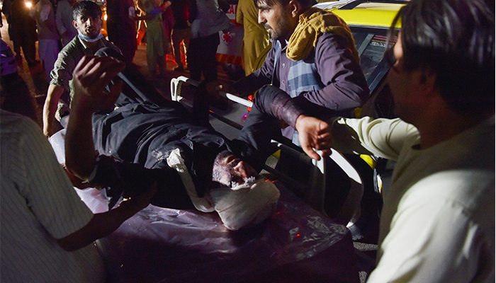 Medical and hospital staff carry an injured man out of a car for treatment after two blasts, which killed at least five and wounded a dozen, outside the airport in Kabul on August 26, 2021. — AFP