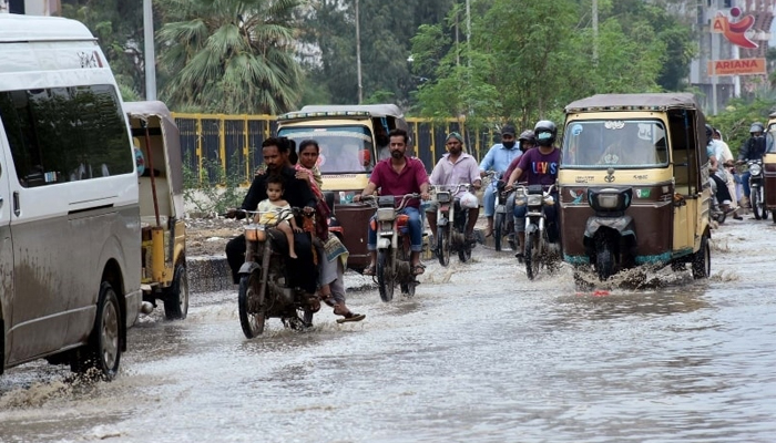 Commuters wade through rainwater after heavy rainfall in Karachi on Saturday — PPI