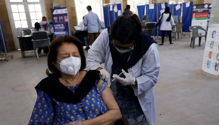 A women can be seen taking coronavirus vaccine — Reuters