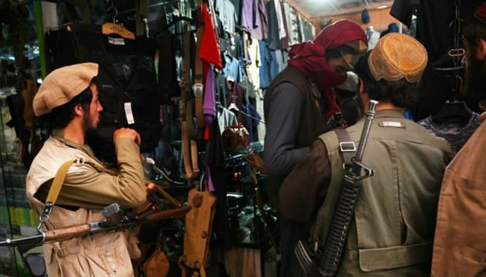 The Taliban fighters are shopping at Bush Market in Kabul. AFP