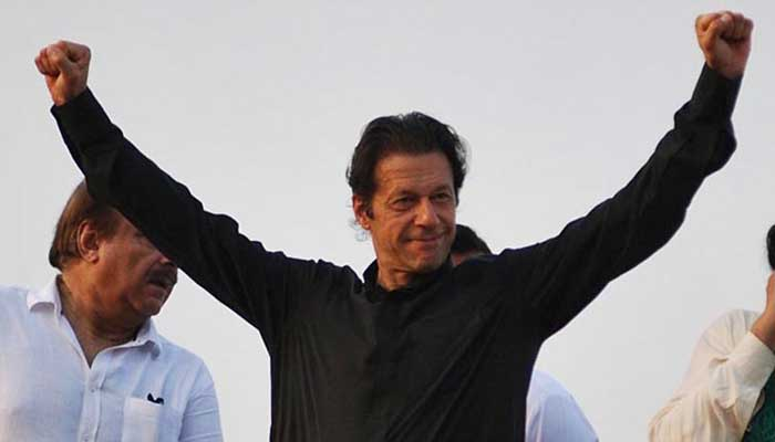 Imran Khan holding his arms in the air in triumph in this Online file photo.