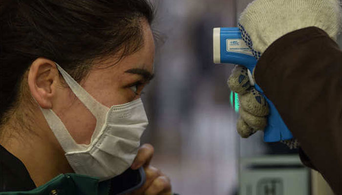 A woman being screened for body temperature. Source: AFP