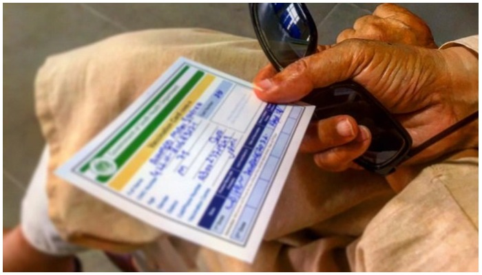 A citizen holds his vaccination card. Photo Geo.tv