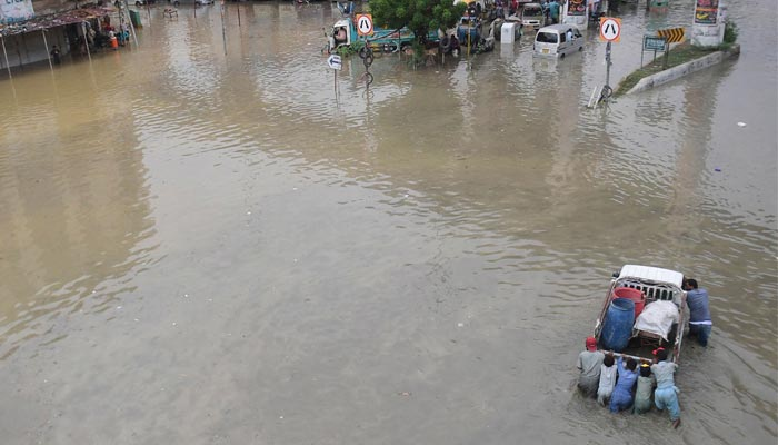 Men push a vehicle through a flooded street after a heavy rainfall in Karachi on September 23, 2021. — AFP