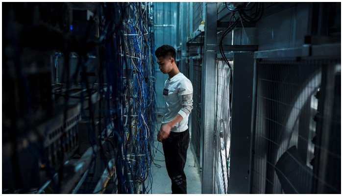 This file photo taken on April 1, 2021 shows a worker adjusting cryptocurrency mining rigs at a cryptocurrency farm in Dujiangyan in Chinas southwestern Sichuan province. Photo: AFP